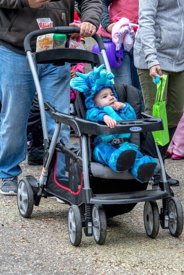 27 de outubro de 2018 Coloma MI EUA; um bebê pequeno bonito em um traje azul do dinossauro aprecia ser empurrado seu carrinho de  fotos de stock