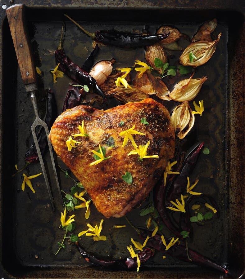 De oven geroosterde borst van Turkije met forsythia eetbare bloemen, uien en Spaanse peper stock afbeelding