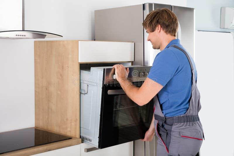 De Oven van technicusin overall installing royalty-vrije stock afbeelding