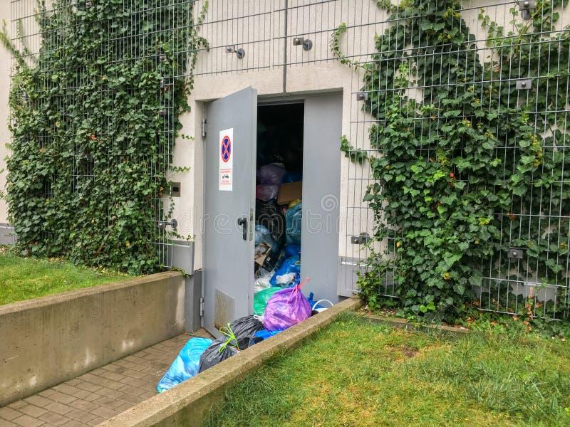 De overbelaste huisvuilbestrating in het gebouw met deur kan ` t CLO stock afbeeldingen