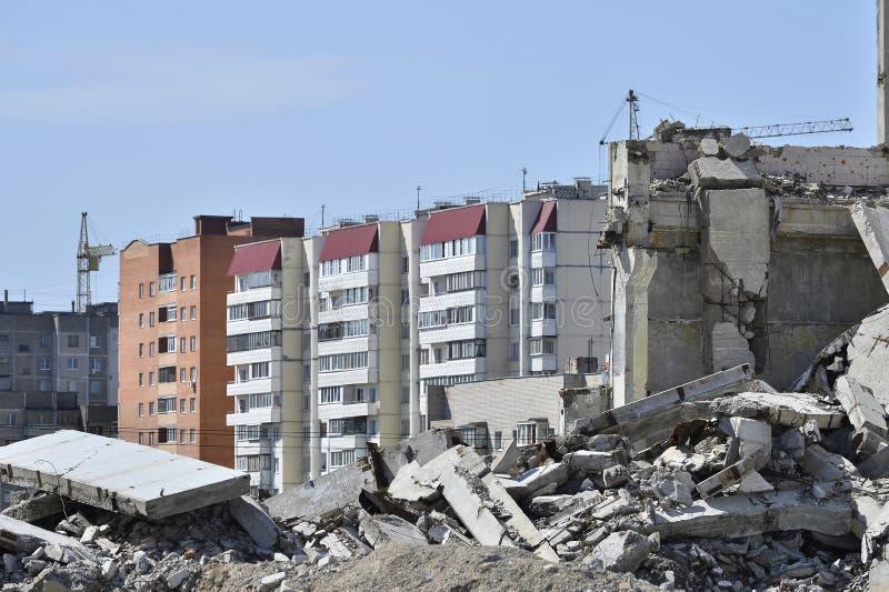 De overblijfselen van de betonconstructie van het gebouw tegen het woondeel van de stad Concept: vernietiging en verwezenlijking royalty-vrije stock fotografie