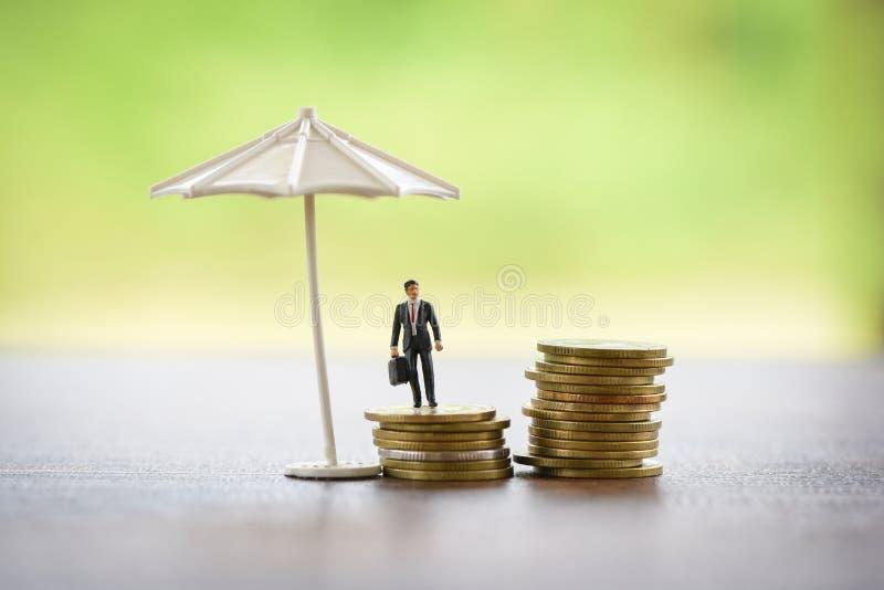 De overeenkomstenconcept van de verkoopverzekering/de aktentas en de paraplu die van de Zakenmanholding muntstuk beschermen royalty-vrije stock afbeelding