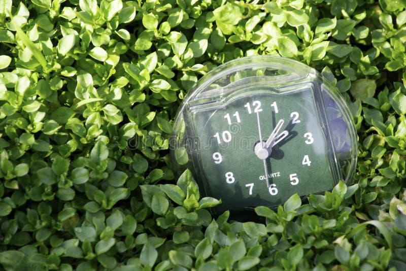 De overgang naar de zomertijd, de aankomst van de lente, de klok op de achtergrond van heldergroen de lentegras met een plaats vo royalty-vrije stock foto's