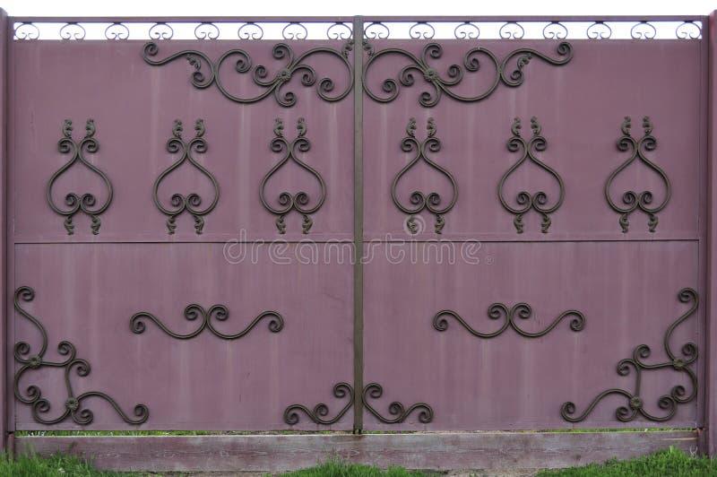 De overladen en mooie poort van de smeedijzeromheining schilderde scharlaken rood en zwart royalty-vrije stock afbeelding