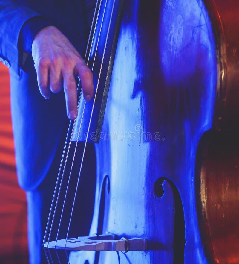 De overlegmening van een speler van de contrabasvioloncel met vocalist en de musical tijdens jazz verbinden het presteren stock afbeeldingen