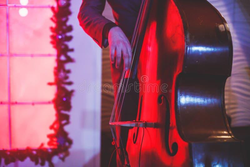 De overlegmening van een speler van de contrabasvioloncel met vocalist en de musical tijdens jazz verbinden het presteren stock fotografie