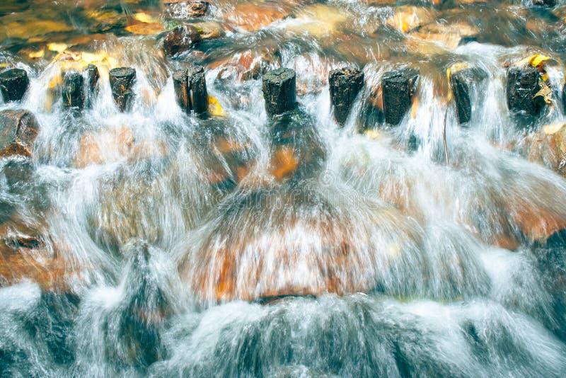 De overstroming van de waterstroom door houten waterkering in de rivier stock fotografie