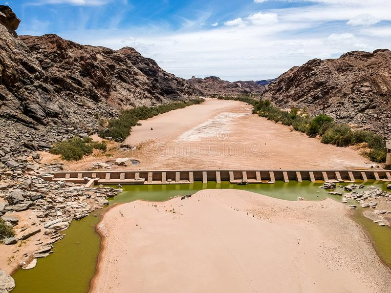 De overweldigende brede mening van de hoek luchthommel van het droge rivierbed en een oude dam met rest van water dichtbij de Het stock foto's