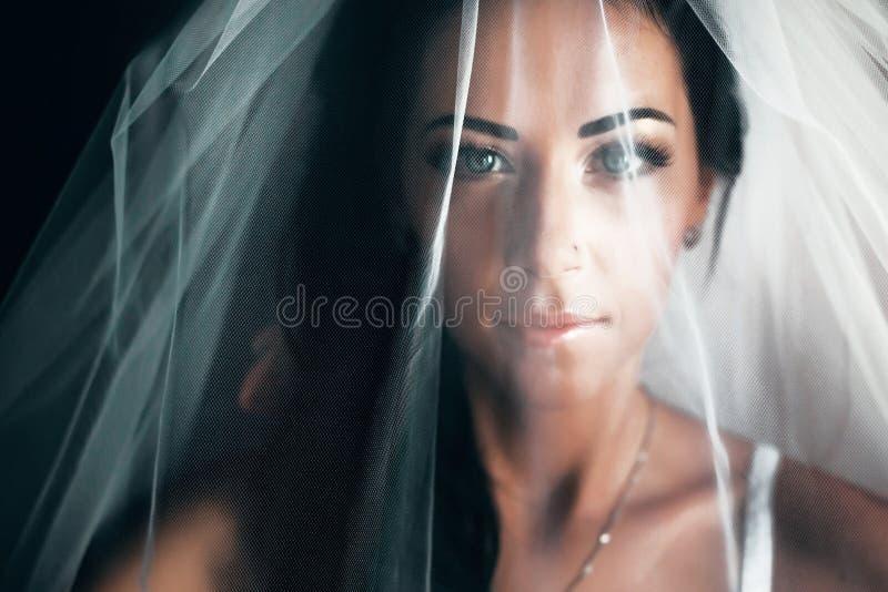 De overweldigende bruid met zwart haar kijkt verborgen onder een sluier stock foto