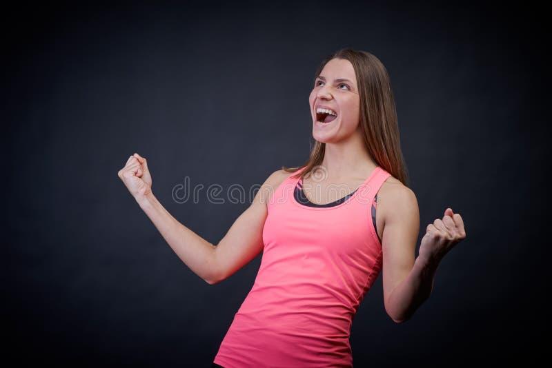 De overweldigende vrouw in sporten eenvormig op een geïsoleerde zwarte achtergrond houdt haar vuisten van geluk, die overwinning  stock afbeelding