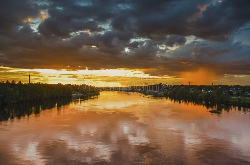 De overweldigende weerspiegeling van zonlicht bij zich het bewegen betrekt en lokale regen op de rivier door de oranje horizon in royalty-vrije stock fotografie