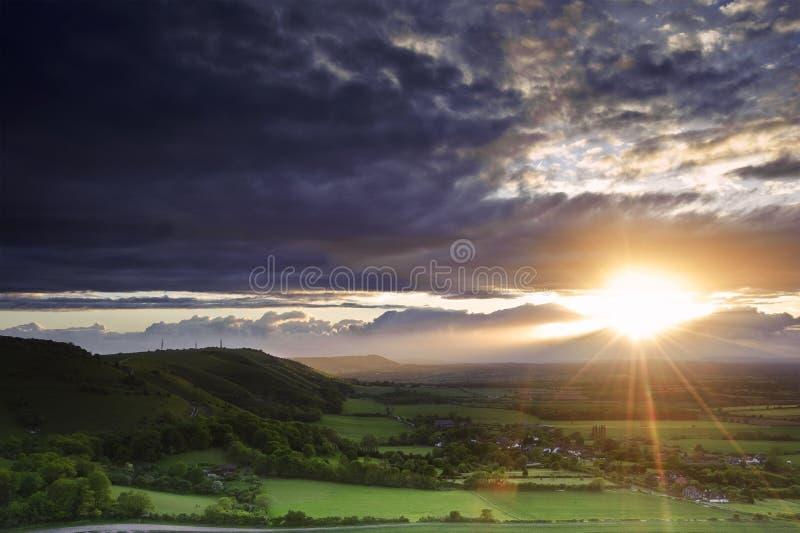 De overweldigende zonsondergang van de Zomer over plattelandslandschap stock fotografie