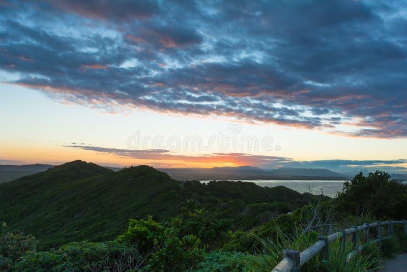 De overweldigende zonsondergangmening over montainsheuvels en oceaan in Byron Bay, Australië royalty-vrije stock afbeelding