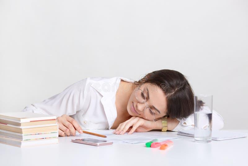 De overwerkte donkerbruine student leunt bij handen op bureau, neemt dutje op het werkplaats, voelt moeheid, draagt wit overhemd, royalty-vrije stock fotografie