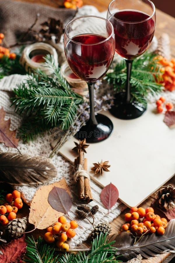 De overwogen wijn in glazen, rode bessen, builen en de herfst vertakt zich op houten lijst royalty-vrije stock foto's