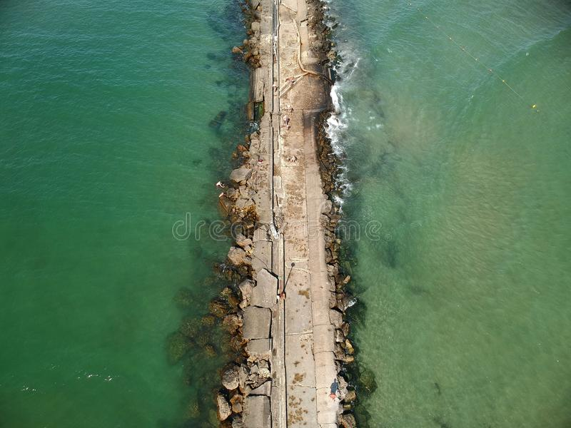 De overzeese die klip hierboven wordt gezien van De golven raken de oude klip Een de zomerdag wanneer het overzees blauw en stil  royalty-vrije stock foto