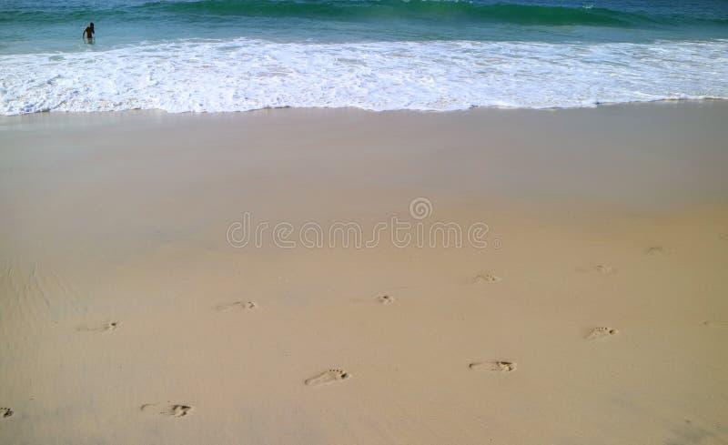 De overzeese golven die op de kust met voetafdrukken langs het zandige strand bespatten stock afbeelding