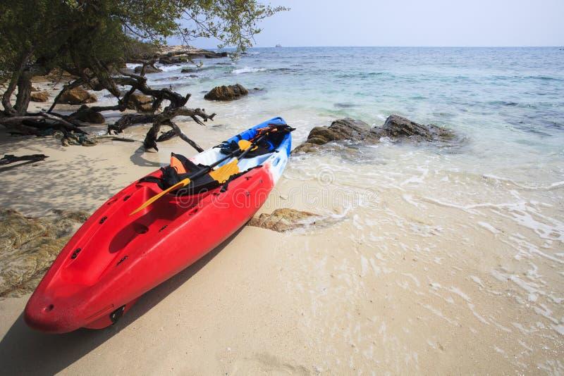 De overzeese kajakkano op overzees zandstrand met mooie aardkust is royalty-vrije stock afbeeldingen