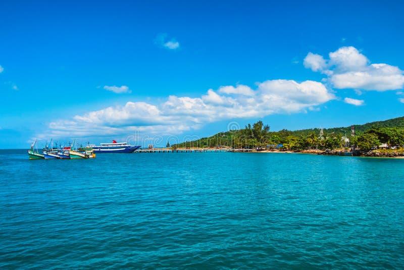 De overzeese kust met turkoois water, houten boten en palmen aan wal stock fotografie