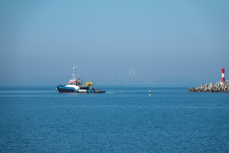 De overzeese sleepboot komt uit de haven royalty-vrije stock afbeelding