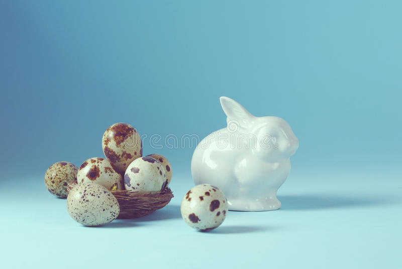 De Pâques de vacances toujours fond de la vie avec les oeufs blancs de lapin et de caille de porcelaine dans le vintage décoratif photographie stock libre de droits