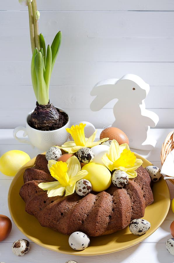 De Pâques toujours la vie, gâteau de Pâques avec les oeufs teints dans un nid, daffodi photos stock