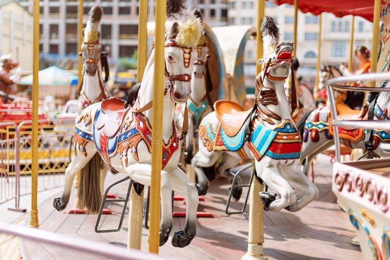 De paarden op Vrolijk Carnaval gaan rond Oude Franse carrousel in een vakantiepark Grote rotonde bij markt in pretpark stock afbeelding