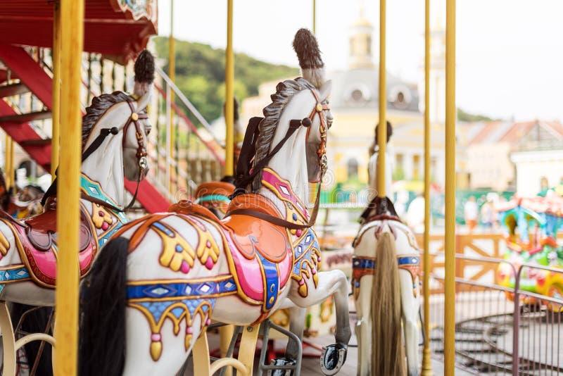 De paarden op Vrolijk Carnaval gaan rond Oude Franse carrousel in een vakantiepark Grote rotonde bij markt in pretpark stock fotografie