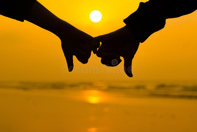 De paarholding elkaar overhandigt het gebruiken van weinig pinkvinger op achtergrond van zonsopgang bij het strand royalty-vrije stock fotografie