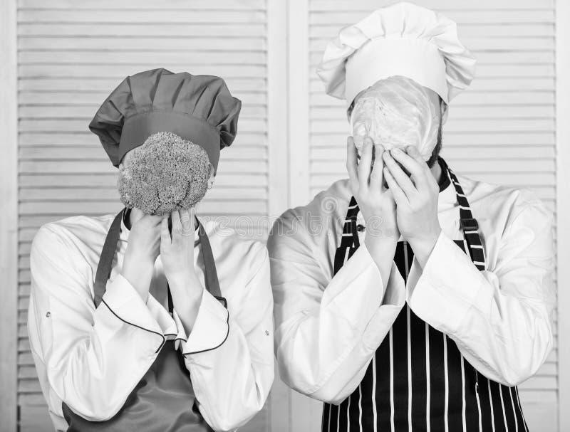 De paarkoks houden kool en broccoli voor gezicht Gezond voedselconcept Paar die gezonde vegetarische maaltijd koken stock fotografie