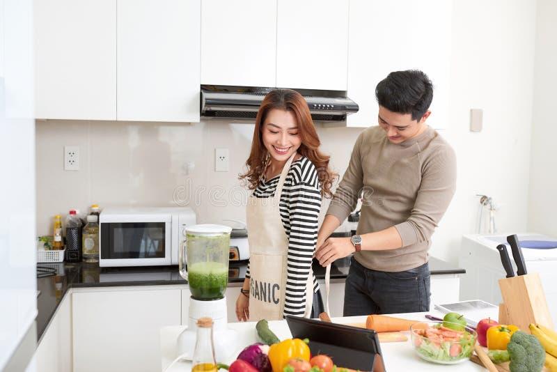 De paarminnaar geniet van samen kokend in huiskeuken, die pre toetreden stock fotografie