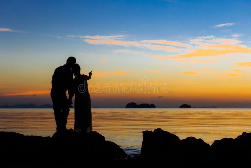 De paarsilhouetten op strand stock afbeeldingen