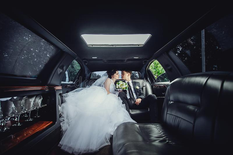 De paarzitting in limo Portret van een mooi jong paar dat rond de stad berijdt stock foto's
