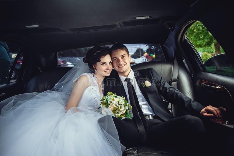 De paarzitting in limo Portret van een mooi jong paar dat rond de stad berijdt stock afbeeldingen