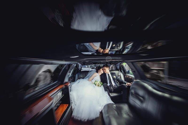 De paarzitting in limo Portret van een mooi jong paar dat rond de stad berijdt Concept beweging stock afbeelding