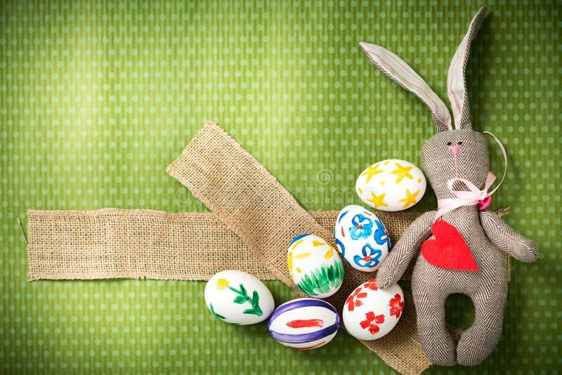 De paaseieren en Pasen-het konijntje liggen op een groene achtergrond royalty-vrije stock afbeeldingen