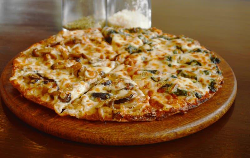 de paddestoel van het pizzabovenste laagje en spinaziekaas op plaat met kruidenfles royalty-vrije stock afbeeldingen