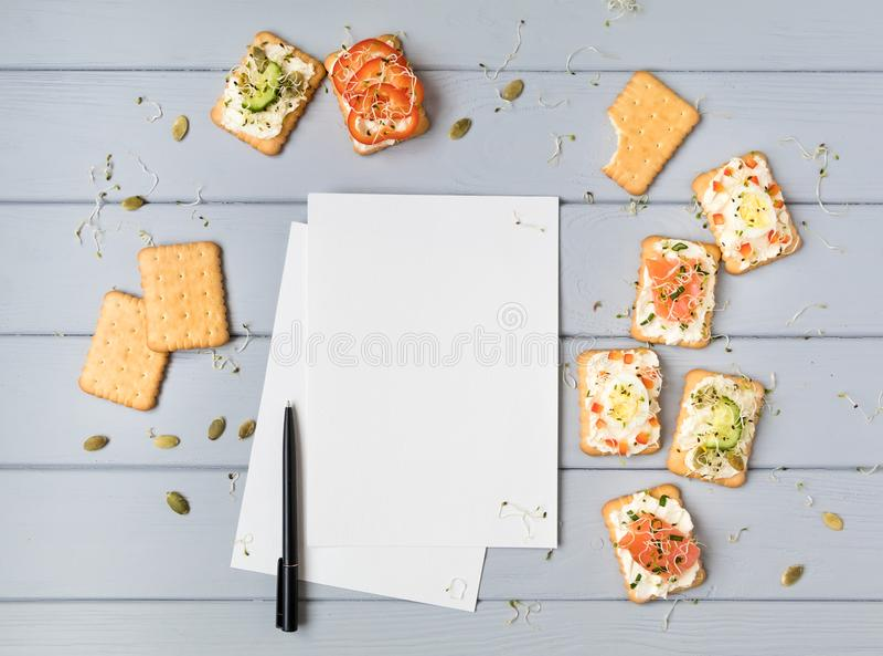 De pagina en de crackers van het receptenboek met roomkaas en diverse bovenste laagjes Voorgerechten op grijze lijst De hoogste v royalty-vrije stock afbeeldingen