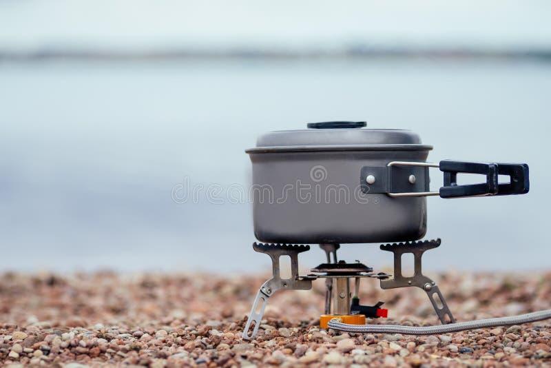 De pan met de pap staat op de gasbrander Camping Stove Op de achtergrond van de rivier royalty-vrije stock afbeeldingen