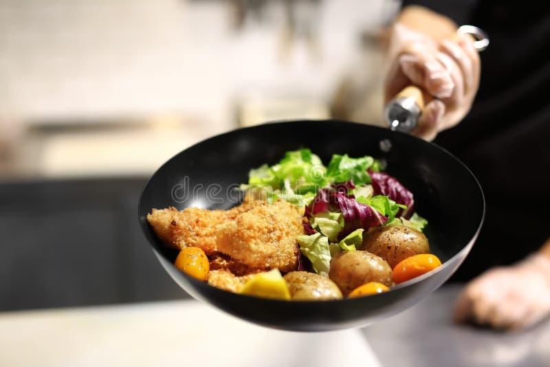 De pan van de chef-kokholding met heerlijke visfilets stock afbeelding