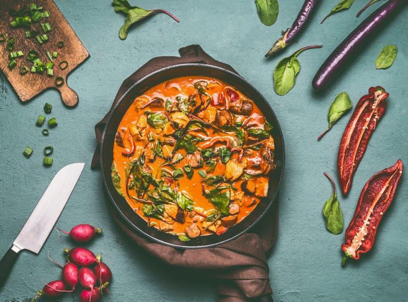 De pan van de groentenkip met kerriesaus op de achtergrond van de keukenlijst met ingrediënten, hoogste vlakke mening, legt stock afbeeldingen