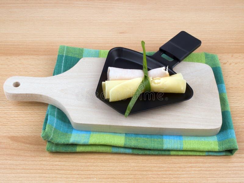 De pan van Raclette met kaas en ham - partijvoedsel stock afbeelding