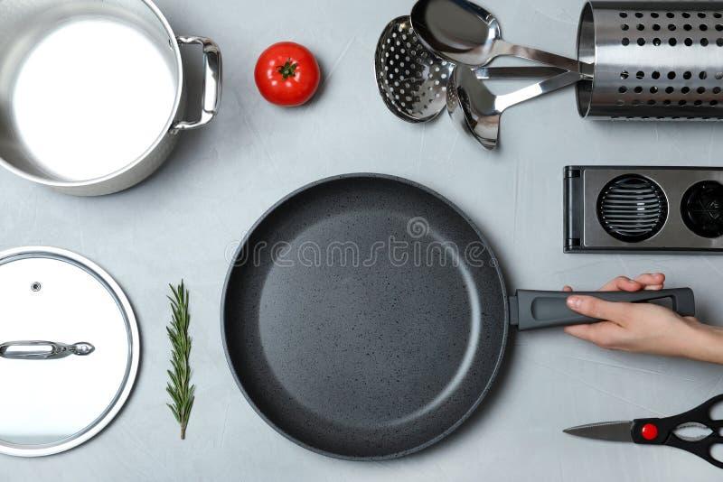 De pan van de vrouwenholding over lijst met schone cookware royalty-vrije stock foto