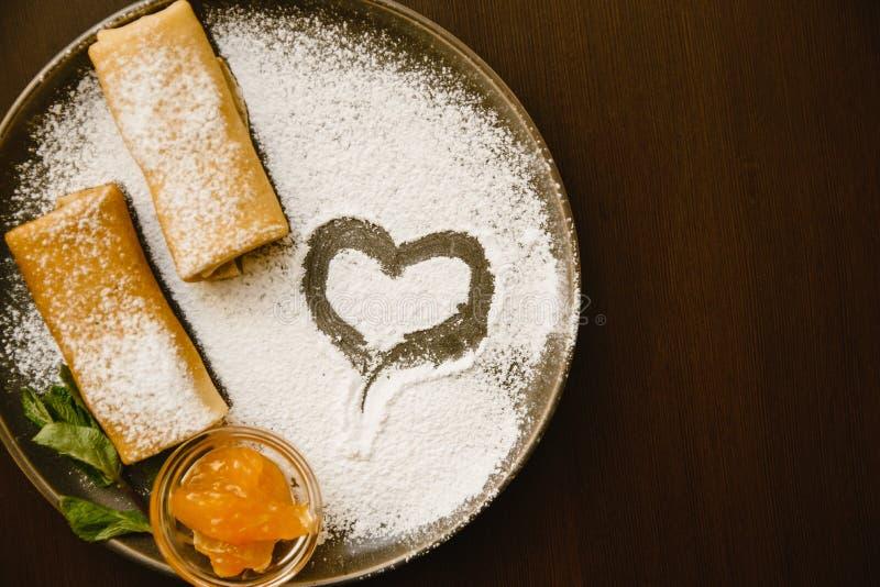 De pannekoeken rolt op een donkere plaat met gepoederde suiker, jam en munt Heerlijk Dessert royalty-vrije stock foto