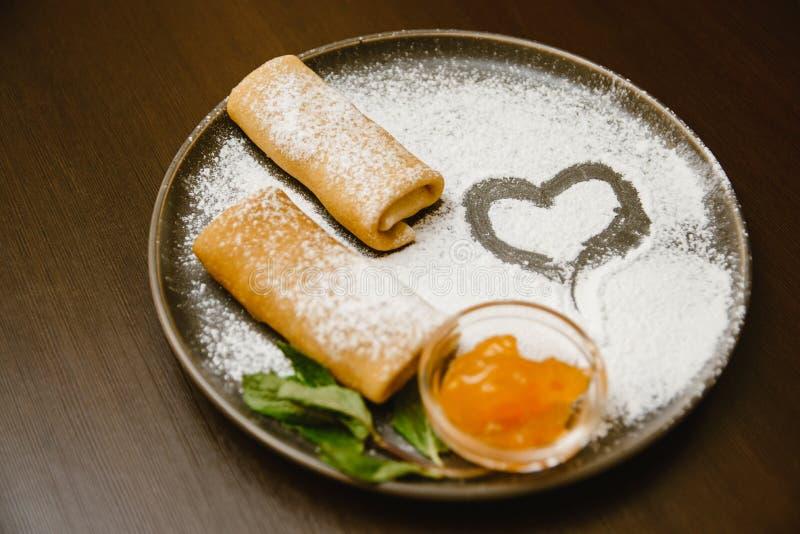 De pannekoeken rolt op een donkere plaat met gepoederde suiker, jam en munt Heerlijk Dessert stock foto