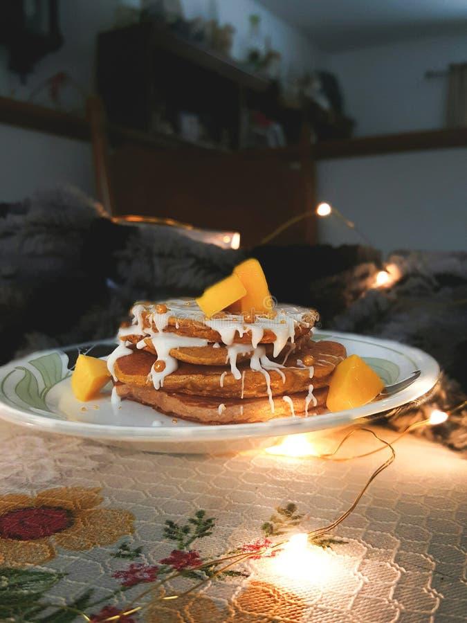 De pannekoeken van de veganistmango met lichten stock afbeeldingen