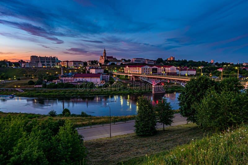 De panoramamening op avond in oude stad op de bank van brede rivier met het gelijk maken van pluizige krullende het rollen cirros royalty-vrije stock foto's