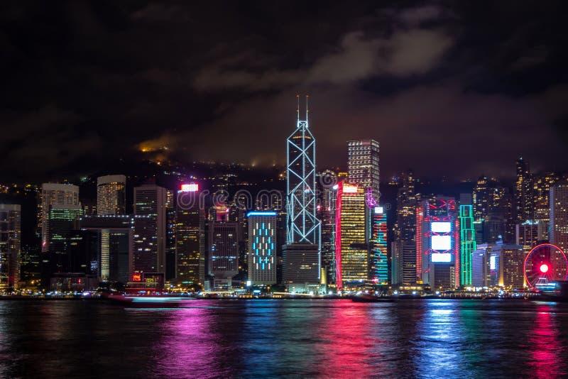 De panoramamening van de stad van Hongkong uit het stadscentrum bij schemer met wolkenkrabbers verlichtte het nadenken in de rivi stock foto