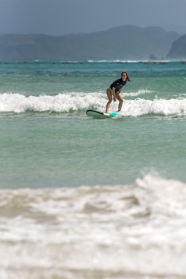 10/06/2017 de Pantau Mawun, Lombok, Indonésia A jovem mulher aprende surfar fotos de stock