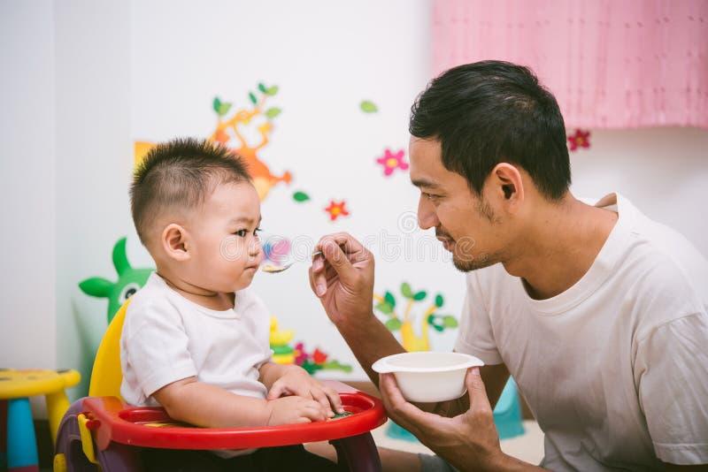 De papa die van de familievader voedende de jongenszoon eten van de voedselbaby royalty-vrije stock afbeelding